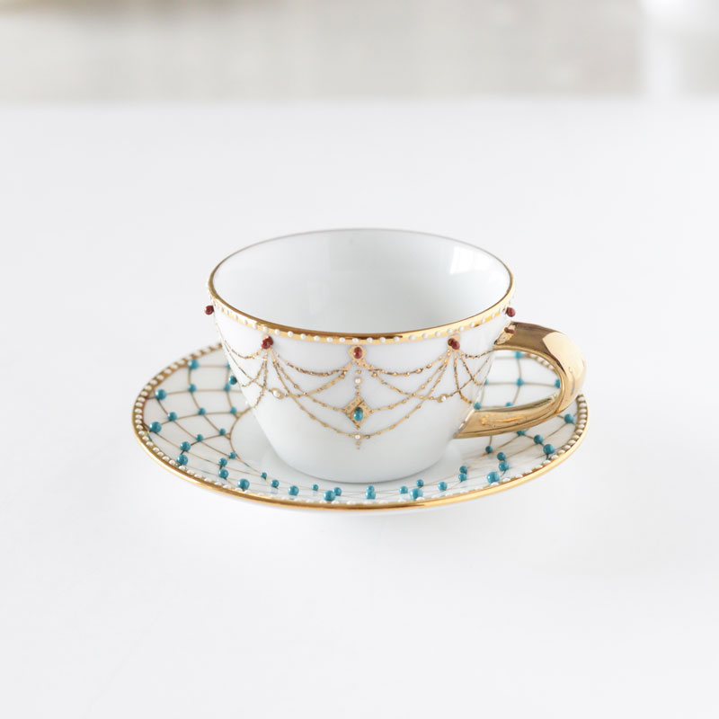 Attaching bijous and dots on the cup and saucer
